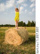 Девочка стоит на барабане с сеном и держит небо. Стоковое фото, фотограф Сергей Шульгин / Фотобанк Лори