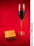 Стеклянный бокал с красным сухим вином и подарочная коробка на красном фоне. Стоковое фото, фотограф Антон Ляшенко / Фотобанк Лори
