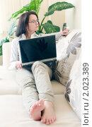 Купить «Девушка в очках с телефоном и ноутбуком на диване», фото № 2023389, снято 7 сентября 2010 г. (c) Никита Жигелев / Фотобанк Лори