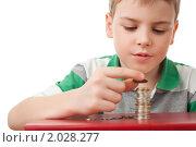 Купить «Мальчик в полосатой футболке складывает монеты», фото № 2028277, снято 9 марта 2010 г. (c) Losevsky Pavel / Фотобанк Лори