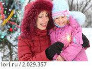 Купить «Мама  с дочкой жгут бенгальский огонь у елки на улице», фото № 2029357, снято 13 декабря 2009 г. (c) Losevsky Pavel / Фотобанк Лори