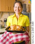 Купить «Женщина с печеной курицей в руках», фото № 2047549, снято 7 октября 2010 г. (c) Яков Филимонов / Фотобанк Лори