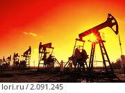 Нефтяные качалки - силуэты на фоне солнца и красного неба. Стоковое фото, фотограф Михаил Коханчиков / Фотобанк Лори
