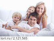 Купить «Счастливая семья лежит на кровати», фото № 2121565, снято 30 сентября 2010 г. (c) Raev Denis / Фотобанк Лори