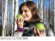 Молодая девушка в клетчатом пальто нюхает два зеленых яблока, фото № 2159369, снято 31 октября 2010 г. (c) Сергей Кузнецов / Фотобанк Лори