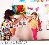 Купить «Девочка с воспитателем рассматривают детские рисунки», фото № 2162137, снято 13 февраля 2010 г. (c) Gennadiy Poznyakov / Фотобанк Лори