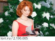 Девушка листает журнал у новогодней елки. Стоковое фото, фотограф Анастасия Шелестова / Фотобанк Лори