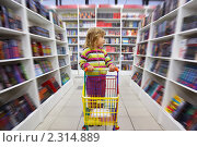 Купить «Девочка с тележкой в книжном магазине», фото № 2314889, снято 19 сентября 2009 г. (c) Losevsky Pavel / Фотобанк Лори