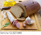 Черный хлеб, колбаса и чеснок на разделочной доске. Стоковое фото, фотограф valentina vasilieva / Фотобанк Лори