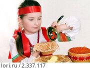 Купить «Девочка в русском народном костюме за столом накладывает деревянной ложкой красную икру на блин. Масленица.», фото № 2337117, снято 11 февраля 2011 г. (c) RedTC / Фотобанк Лори