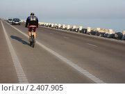 Купить «Велосипедист на дороге, идущей вдоль моря», фото № 2407905, снято 24 мая 2019 г. (c) valentina vasilieva / Фотобанк Лори