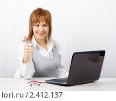 Купить «Привлекательная улыбающаяся девушка в офисе с ноутбуком», фото № 2412137, снято 3 декабря 2010 г. (c) Татьяна Гришина / Фотобанк Лори