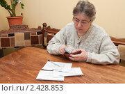 Женщина считает деньги на оплату коммунальных услуг. Стоковое фото, фотограф Марина Славина / Фотобанк Лори