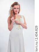 Блондинка в белом платье с цветком в волосах на сером фоне. Стоковое фото, фотограф Антон Романов / Фотобанк Лори