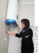 Купить «Девушка пытается разобраться  с  электроводонагревателем в ванной комнате», эксклюзивное фото № 2477333, снято 16 апреля 2011 г. (c) Анна Мартынова / Фотобанк Лори