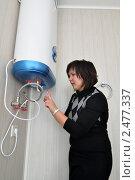 Купить «Девушка пытается разобраться  с  электроводонагревателем в ванной комнате», эксклюзивное фото № 2477337, снято 16 апреля 2011 г. (c) Анна Мартынова / Фотобанк Лори