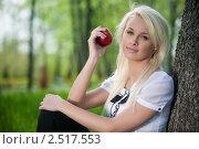 Девушка сидит в парке с яблоком в руках. Стоковое фото, фотограф Андрей Батурин / Фотобанк Лори