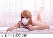 Девушка с чашкой чая лежит в кровати. Стоковое фото, фотограф Дмитрий Рогатнев / Фотобанк Лори
