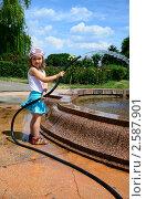 Девочка играет с резиновым шлангом у фонтана. Стоковое фото, фотограф Людмила / Фотобанк Лори