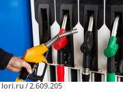 Купить «Мужчина на бензоколонке держит в руке заправочный пистолет с бензином или дизельным топливом для автомобиля», фото № 2609205, снято 19 июня 2011 г. (c) Илья Андриянов / Фотобанк Лори