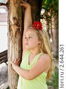 Девочка с красным цветком в волосах стоит у дерева в парке. Стоковое фото, фотограф Елена Сикорская / Фотобанк Лори