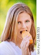 Купить «Молодая девушка ест булочку», фото № 2668553, снято 12 июня 2011 г. (c) BestPhotoStudio / Фотобанк Лори