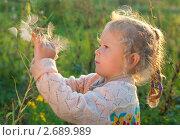 Девочка разглядывает растение в саду. Стоковое фото, фотограф Олег Кириллов / Фотобанк Лори