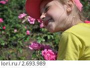 Улыбающаяся девочка среди розовых роз. Стоковое фото, фотограф Дарина Бабий / Фотобанк Лори
