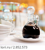 Соевый соус в стеклянном графине стоит на накрытом столе. Стоковое фото, фотограф IEVGEN IVANOV / Фотобанк Лори