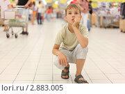Купить «Уставший мальчик сидит на корточках посреди супермаркета», фото № 2883005, снято 4 июля 2010 г. (c) Losevsky Pavel / Фотобанк Лори