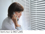 Девушка стоит  у  окна и разговаривает  по телефону. Стоковое фото, фотограф Дарина Бабий / Фотобанк Лори