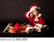 Малыш в костюме Санта Клауса на темном фоне. Стоковое фото, фотограф Наташа Чапкайло / Фотобанк Лори