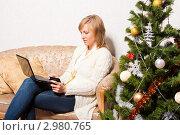Купить «Женщина с ноутбуком сидит на диване возле елки», фото № 2980765, снято 19 декабря 2018 г. (c) Ольга Хорькова / Фотобанк Лори