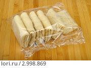 Купить «Пакет замороженных блинчиков на деревянном столе», фото № 2998869, снято 1 декабря 2011 г. (c) Руслан Григолава / Фотобанк Лори