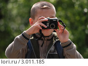 Мальчик фотографирует на природе (2011 год). Редакционное фото, фотограф OlgaM. / Фотобанк Лори