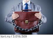 Купить «Мужчина в сером офисном костюме с цепью на руках держит портфель», фото № 3016509, снято 12 октября 2011 г. (c) Elnur / Фотобанк Лори