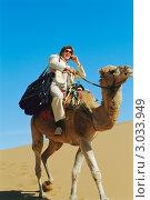 Купить «Мужчина с мобильным телефоном верхом на верблюде в пустыне», фото № 3033949, снято 23 октября 2019 г. (c) Monkey Business Images / Фотобанк Лори