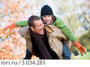 Счастливый отец держит сына на спине в осеннем парке. Стоковое фото, фотограф Monkey Business Images / Фотобанк Лори
