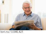 Седой мужчина читает газету дома на софе. Стоковое фото, фотограф Monkey Business Images / Фотобанк Лори