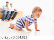 Купить «Малыш ползает по полу в комнате с родителями на заднем плане», фото № 3054829, снято 14 января 2007 г. (c) Monkey Business Images / Фотобанк Лори