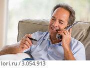 Мужчина, сидя на диване разговаривает по мобильному телефону и смотрит на кредитную карту в руках. Стоковое фото, фотограф Monkey Business Images / Фотобанк Лори