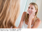 Купить «Улыбающаяся девушка наносит крем на лицо», фото № 3061277, снято 2 февраля 2006 г. (c) Monkey Business Images / Фотобанк Лори