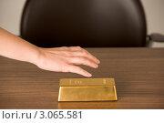 Купить «Рука берет золотой слиток со стола», фото № 3065581, снято 15 декабря 2017 г. (c) Monkey Business Images / Фотобанк Лори