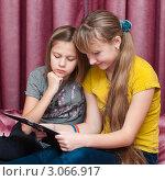 Купить «Две девочки с фотоальбомом», эксклюзивное фото № 3066917, снято 2 декабря 2011 г. (c) Игорь Низов / Фотобанк Лори