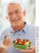 Купить «Улыбающийся пожилой мужчина ест фруктовый салат», фото № 3069521, снято 26 июня 2007 г. (c) Monkey Business Images / Фотобанк Лори