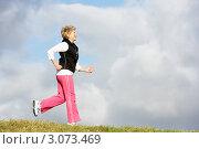 Купить «Пожилая женщина в розовых брюках бежит на фоне облачного неба», фото № 3073469, снято 12 ноября 2008 г. (c) Monkey Business Images / Фотобанк Лори