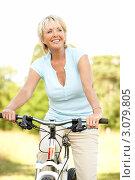 Купить «Радостная зрелая блондинка на велосипеде летом», фото № 3079805, снято 24 июня 2009 г. (c) Monkey Business Images / Фотобанк Лори