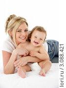 Купить «Красивая молодая женщина с ребенком лежит на полу», фото № 3088421, снято 9 апреля 2009 г. (c) Monkey Business Images / Фотобанк Лори