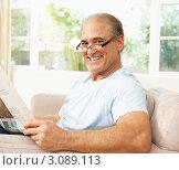 Купить «Портрет улыбающегося мужчины средних лет в очках на диване с газетой», фото № 3089113, снято 10 августа 2009 г. (c) Monkey Business Images / Фотобанк Лори