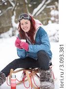 Купить «Красивая девушка сидит на санках зимой и пьет напиток из термоса», фото № 3093381, снято 5 января 2010 г. (c) Monkey Business Images / Фотобанк Лори